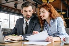 买卖人有工作午餐在看妇女藏品合同的餐馆坐的人浏览膝上型计算机 免版税库存图片
