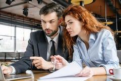 买卖人有工作午餐在餐馆坐的研究在网上膝上型计算机 库存照片