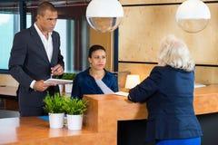 买卖人谈话与接待员在办公室 免版税库存图片