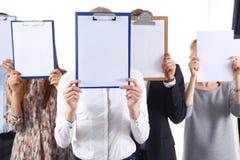 买卖人队拿着文件夹在白色背景隔绝的面孔附近 买卖人 库存照片