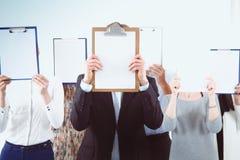 买卖人队拿着文件夹在白色背景隔绝的面孔附近 买卖人 免版税库存图片