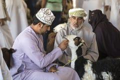 买卖山羊的人在市场上 免版税库存图片