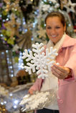 购买圣诞节雪花装饰品商店的妇女 免版税图库摄影