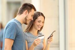 买在与信用卡和巧妙的电话的线的顾客 免版税库存图片
