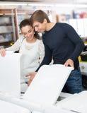 买在电器商店的家庭夫妇新的衣裳洗衣机 免版税库存图片
