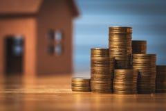 买它自己的金钱的一个新的家的挽救金钱在存钱罐中 最便宜和税 免版税库存照片