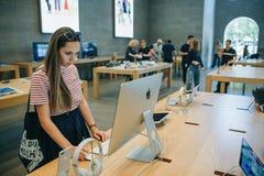 买家在正式苹果计算机商店寻找购买的新的IMac在柏林 库存照片