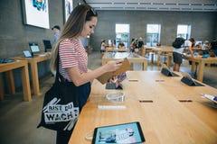 买家在苹果计算机正式商店选择买一新的iPad在柏林 免版税库存照片