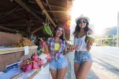 买异乎寻常的果子和饮料椰子的美丽的女孩,当购物在传统亚洲街市愉快微笑时 免版税库存照片