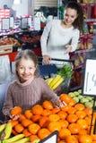 买成熟果子的家庭顾客 免版税库存照片