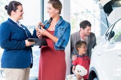 买新的汽车的家庭在汽车经销商陈列室里 免版税图库摄影