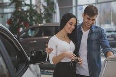 买新的汽车的愉快的夫妇在经销权沙龙 免版税库存图片