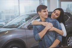 买新的汽车的愉快的夫妇在经销权沙龙 免版税库存照片