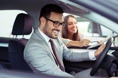 买新的汽车的愉快的顾客画象 免版税库存照片