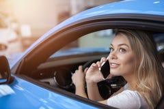 买新的汽车的美丽的年轻女人在经销权 库存图片