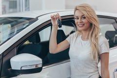 买新的汽车的美丽的年轻女人在经销权 图库摄影