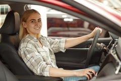 买新的汽车的美丽的年轻女人在经销权 免版税库存照片