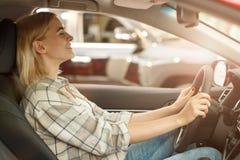 买新的汽车的美丽的年轻女人在经销权 免版税图库摄影
