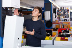 买新的热化水壶的年轻人在电器商店 库存照片