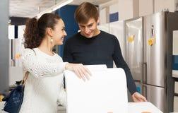 买新的衣裳洗衣机的夫妇 免版税库存图片