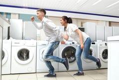 买新的洗衣机的愉快的家庭夫妇 免版税库存图片