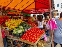 买新鲜的水果和蔬菜的人们在地方市场上 库存图片