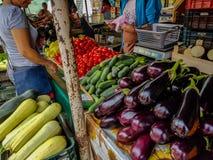 买新鲜的水果和蔬菜的人们在地方市场上 库存照片