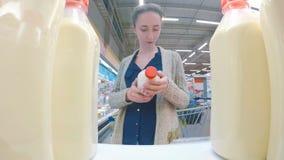 买新鲜的牛奶的妇女在超级市场 免版税库存照片