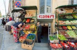 买新鲜的水果和蔬菜的妇女在老城市室外农夫商店  免版税库存图片