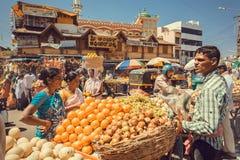 买新鲜水果和桔子在室外市场的妇女有许多顾客的在繁忙的亚洲街道上 免版税库存图片