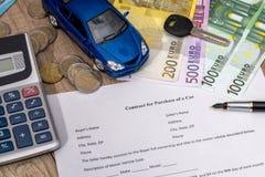 买有欧元、笔、计算器和玩具汽车的一辆汽车 库存图片