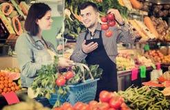 买果子的微笑的男性售货员帮助的顾客  免版税图库摄影