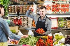 买果子的年轻男性售货员帮助的顾客和 库存照片