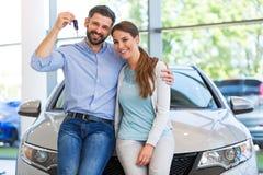 买汽车的年轻夫妇 库存照片