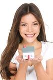 买的新的家庭概念-拿着微型房子的妇女 免版税库存照片