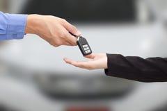 买的汽车的概念 供以人员给一辆关键汽车女商人  免版税库存图片