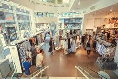 买穿戴里面的顾客有男性和女性衣裳的普遍的嗯商店在挂衣架 免版税图库摄影