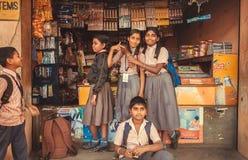 买笔记本和笔的孩子在固定式商店在类以后 库存图片