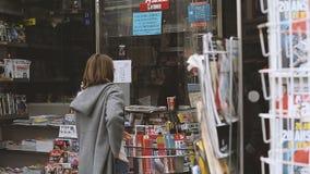 买经济学家金融时报的妇女在新闻报亭 影视素材