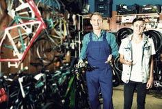 买自行车的卖主帮助的少年 免版税库存图片