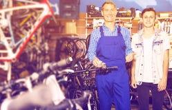 买自行车的卖主帮助的少年 库存照片
