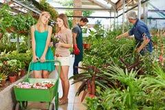 买花的妇女在托儿所商店 免版税库存图片