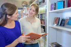 买议程的妇女在固定式商店 图库摄影