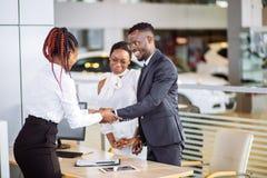 买车的顾客在售车行 妇女和人符号交换 图库摄影