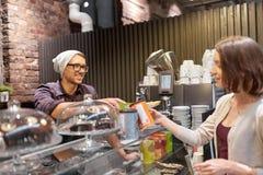 买柴拿铁饮料的愉快的妇女在素食主义者咖啡馆 免版税库存照片