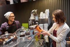 买柴拿铁饮料的愉快的妇女在素食主义者咖啡馆 免版税图库摄影