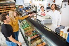 购买从推销员的夫妇肉在商店 免版税图库摄影