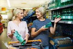 购买水的女性顾客在大型超级市场 免版税库存图片