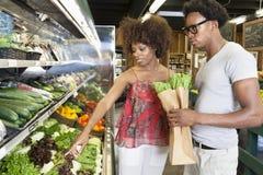 买绿色菜的年轻非裔美国人的夫妇在超级市场 库存图片