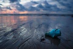 乱丢海洋的塑料垃圾在海滩在日落期间,酸值朗塔,泰国 免版税库存照片